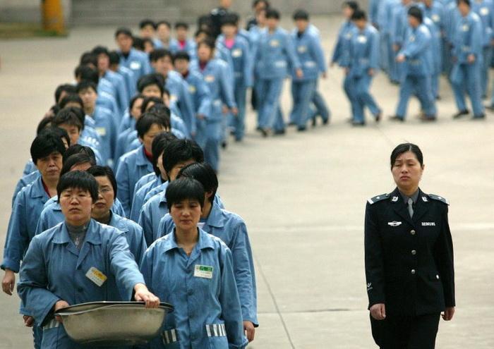 Заключённые под наблюдением охраны в тюрьме Нанкина, Китай, 11 апреля 2005 года. В провинции Гуандун разработали план по закрытию трудовых лагерей. Фото: STR/AFP/Getty Images