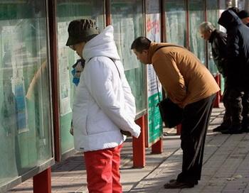 Люди, читающие ежедневные газеты, расположенные на общественных информационных табло в Пекине. Фото: Teh Koon/AFP/Getty Images
