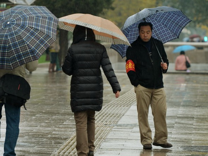 Доброволец по охране порядка дежурит возле Большого народного зала, Пекин, 10 ноября. Фото: Mark Ralston/AFP/Getty Images