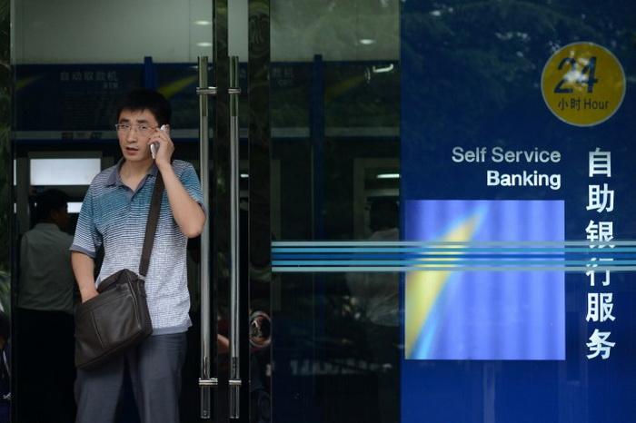 Клиент разговаривает по мобильному телефону у входа в банк в Пекине, 25 июня 2013 года. Фото: Wang Zhao AFP/Getty Images