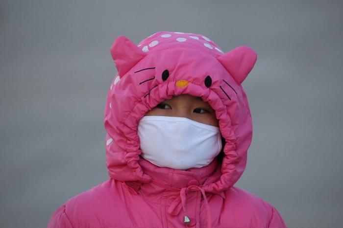 Девочка на площади Тяньаньмэнь надела маску, чтобы защититься от смога, 17 января 2013 года, Пекин. Фото: Feng Li/Getty Images