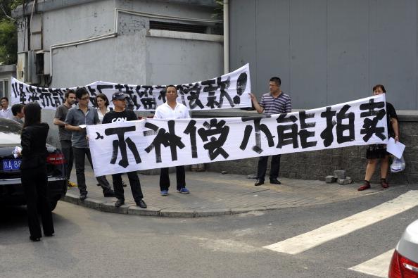 На плакатах написано: «Никаких аукционов по продаже земли! Никаких компенсаций!» Фото: ChinaFotoPress / Getty Images