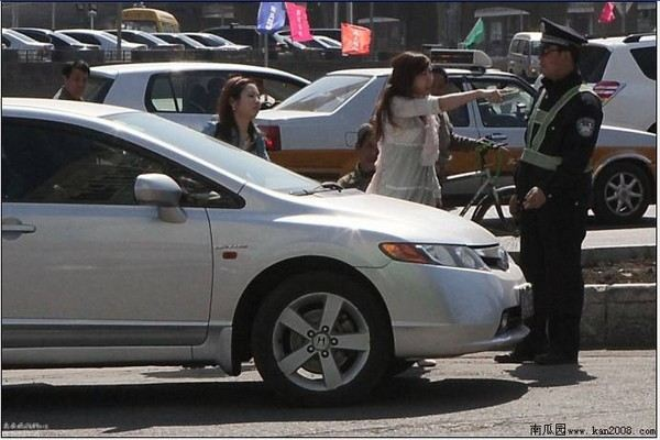 Женщина, ехавшая без прав, угрожает остановившему её дорожному полицейскому. Провинция Цзилинь. Апрель 2011 год. Фото с kanzhongguo.com