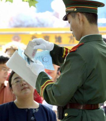 Фото : Китайская военизированная охрана проверяет паспорт американского гражданина, претендующего на получение визы, Пекин, 17 мая 2004 года. (Goh Chai Hin/Getty Images)