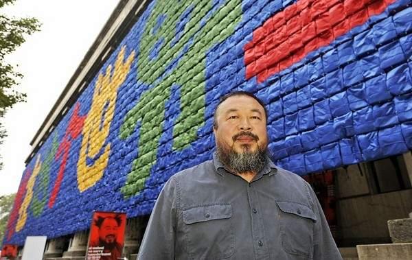 Ай Вэйвэй на фоне своей инсталляции «Стена из школьных рюкзаков», сделанная в память о погибших под развалинами некачественных зданий школ детей во время землетрясения в Сычуани в 2008 году. Фото: JOERG KOCH/Getty Images