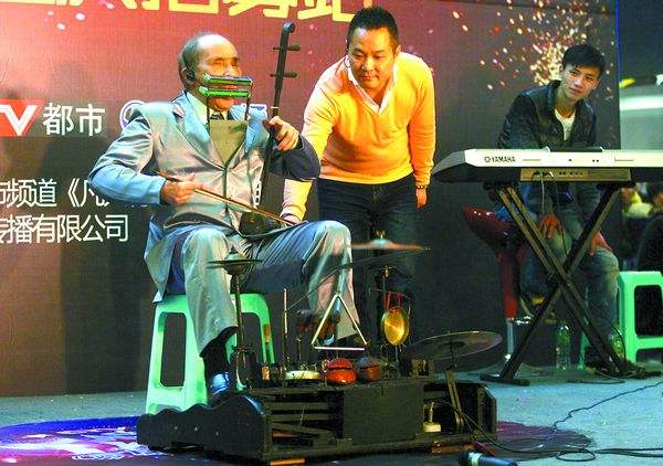 Вэнь Хуацюн исполняет народную мелодию, играя одновременно на 15 инструментах. Фото: cqcb.com