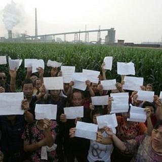 Жители деревни на фоне завода держат медицинские заключения, подтверждающие отравление свинцом. Провинция Хунань. 2009 год. Фото: Sound Of Hope