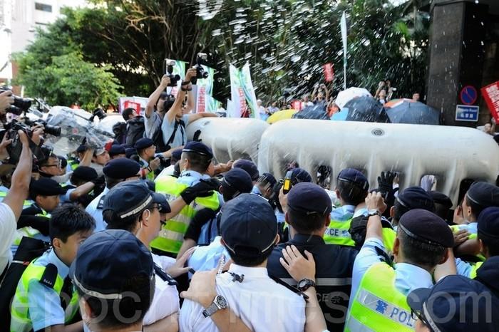 Полицейские усмиряют демонстрантов перцовой водой. Гонконг. Июнь 2012 год. Фото: The Epoch Times