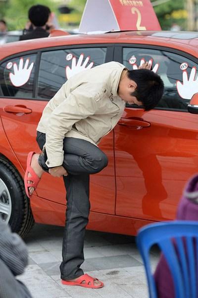 Участник соревнований «кто сможет дольше всех прикасаться к автомобилю БМВ». Май 2012 год. Фото с news.ifeng.com