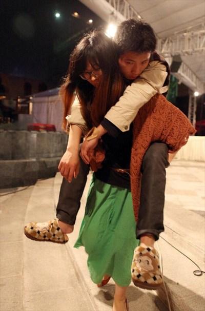 Обессилевшего участника соревнований уносит сестра. Май 2012 год. Фото с news.ifeng.com