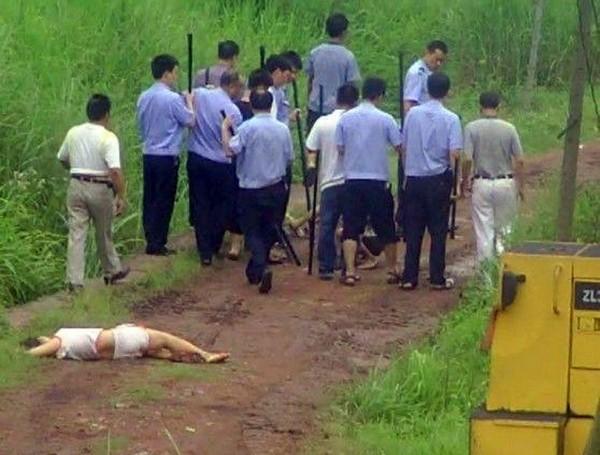 Избитая полицейскими женщина осталась лежать на дороге. Провинция Хунань 2011 год. Фото с kanzhongguo.com