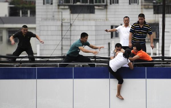 После безуспешных попыток вернуть конфискованный полицией за незаконное вождение автомобиль, женщина залезла на крышу полицейского участка и попыталась покончить с собой. Город Шэньчжэнь. 28 сентября 2011 год. Фото: ifeng.com