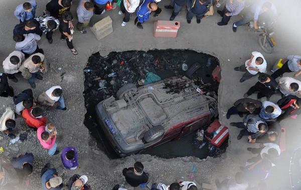 Автомобиль провалился в образовавшуюся на дороге яму. Город Тяньцзинь. 28 сентября 2011 год. Фото: ifeng.com