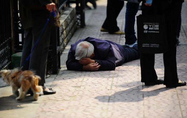 74-лений дедушка внезапно упал на остановке. Никто из стоящих вокруг не попытался ему помочь. Город Сиань провинции Шэньси. 20 сентября 2011 год. Фото: ifeng.com