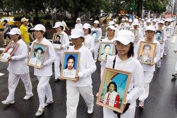 Последователи Фалуньгун в белых траурных одеждах несут фотографии своих единомышленников, погибших в континентальном Китае от репрессий со стороны компартии. Тайвань. Фото: The Epoch Times