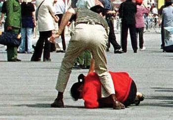 Полицейский агент арестовывает последовательницу Фалуньгун. Китай. Фото: minghui.org