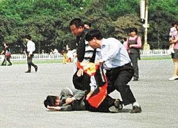 Полицейские агенты арестовывают сторонницу Фалуньгун, рассказывающую на улице людям о репрессиях своих единомышленников коммунистическим режимом. Фото: minghui.org