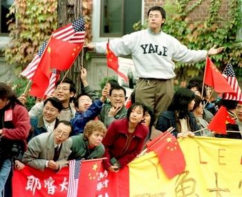Когда высокопоставленные китайские чиновники приезжают с визитом в другие страны, местные посольства КНР используют членов студенческих союзов, чтобы красными флагами или громкими криками загородить многочисленные акции протестов против режима КНР. На фото студент перед приездом китайской делегации своим телом загораживает транспарант протестующих. Фото: Франс Пресс