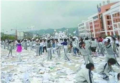 Китайские выпускники школ радостно рвут и выбрасывают учебники и тетради, прощаясь со школой. Июнь 2012 год. Фото с epochtimes.com