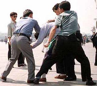 Полицейские агенты задерживают сторонника Фалуньгун, рассказывающего людям о преследовании его единомышленников коммунистическим режимом. Фото: minghui.org