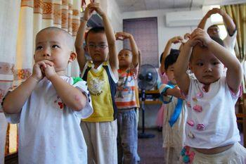 Ученики традиционной конфуцианской школы делают жест почтения перед портретом Конфуция. Провинция Хайнань. Август 2011 год. Фото с hkkzxt.org
