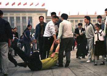 Китайские полицейские арестовывают последователя Фалуньгун. Фото: minghui.org