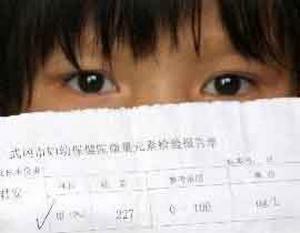 Девочка держит медицинское заключение о том, что в её крови повышенно содержание свинца. Фото: «Босюн»