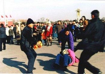 Полицейские агенты арестовывают последовательницу Фалуньгун, рассказывающую прохожим о политике подавления её единомышленников коммунистическим режимом. Китай. Фото: minghui.org