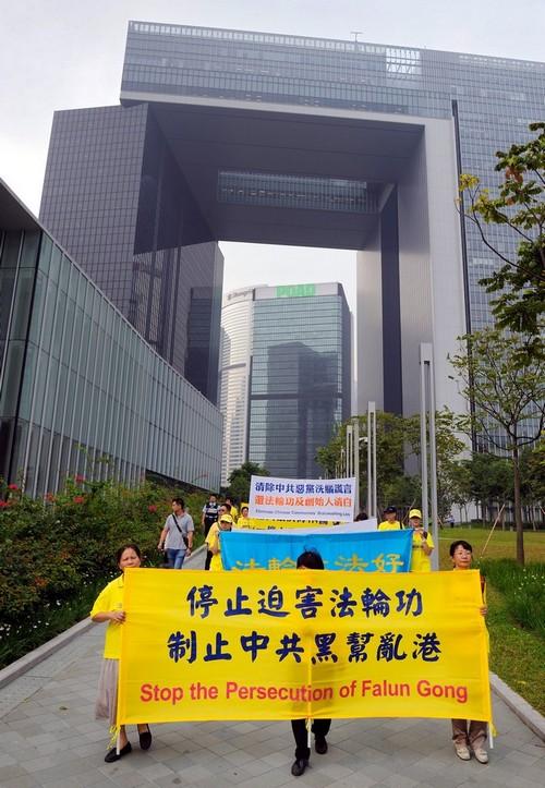 Шествие последователей Фалуньгун в Гонконге. Надпись на плакате на китайском языке: «Остановить преследование Фалуньгун. Пресечь внедрение в Гонконг коммунистической банды». Октябрь 2012 год. Фото: minghui.org