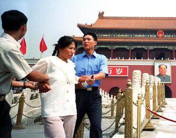 Полицейские арестовывают сторонницу Фалуньгун, которая вышла на площадь Тяньаньмэнь с протестом против подавления властями её практики. Пекин. Фото: minghui.org