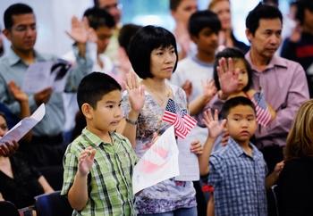 Семья китайцев принимает присягу на верность США во время церемонии получения американского гражданства. Лос-Анджелес. Фото: Kevork Djansezian/Getty Images