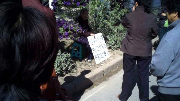 90-летняя мать арестованного последователя Фалуньгун перед полицейским участком требует освобождения своего сына, который находится при смерти в больнице. Провинция Хэйлунцзян. Сентябрь 2011 год