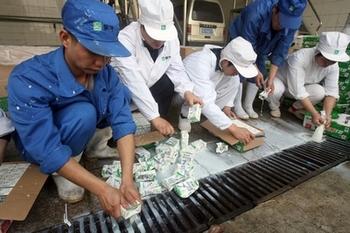 На фото сотрудники компании «Мэнню» уничтожают партию проблемного молока. Однако многие уверены, что это показуха, а молоко из этой партии уже давно реализовано. Фото: AFP PHOTO