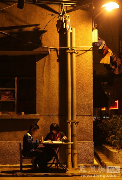 13-летняя Сяо Юй со своим братом делает уроки на улице под светом фонаря. На протяжении уже семи лет у них в квартире нет воды и света, так как зарплаты родителей не хватает на оплату этих услуг. При этом ученица 6-го класса Сю Юй является второй по успеваемости в классе. 5 декабря 2011 год. Фото: Чен Биншен