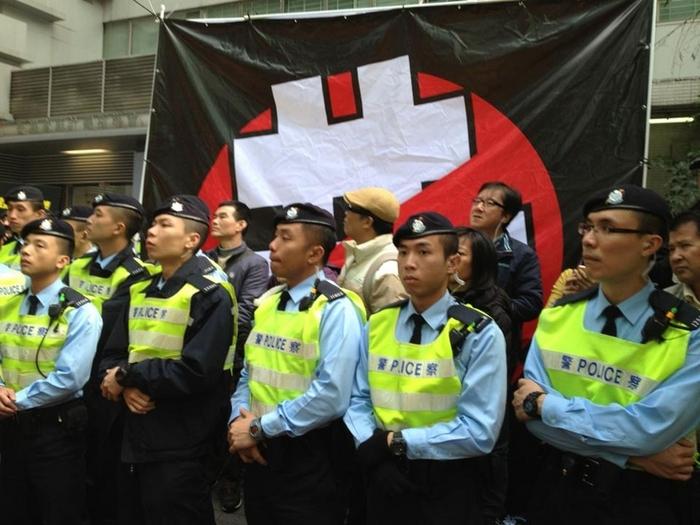Полицейские возле представительства Пекина закрыли собой плакат с перечёркнутым иероглифом, означающим «компартия». Протесты в Гонконге. Январь 2013 года. Фото: The Epoch Times