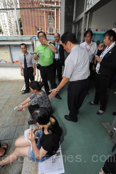 Нанятые режимом компартии люди сели возле входа в задние Caritas, пытаясь препятствовать людям входить внутрь. Гонконг. 18 августа 2012 год. Фото: The Epoch Times