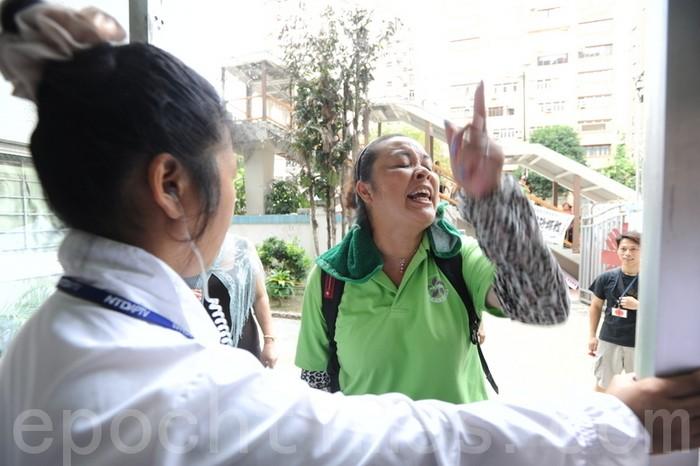 Нанятая компартией женщина осыпает руганью работников Caritas не пускающих её войти в здание, где проходит конкурс китайского танца. Гонконг. 18 августа 2012 год. Фото: The Epoch Times