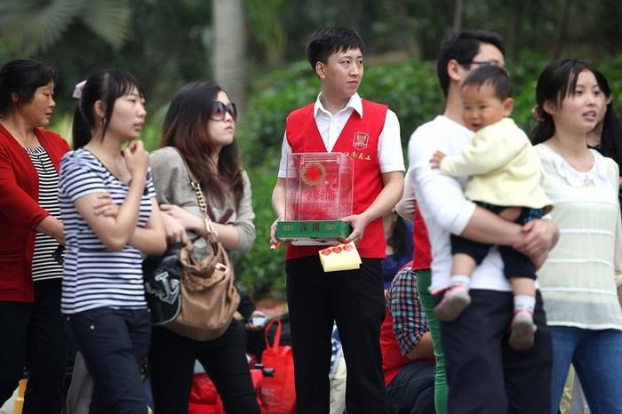 Волонтёр организации «Красный крест» безуспешно пытается привлечь прохожих пожертвовать деньги на помощь пострадавшим от землетрясения в Сычуани. Апрель 2013 год. Фото с epochtimes.com