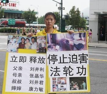 Лю Цзюньчень с плакатами рассказывает людям о преследовании своей семьи в Китае правящим режимом. Фото с secretchina.com