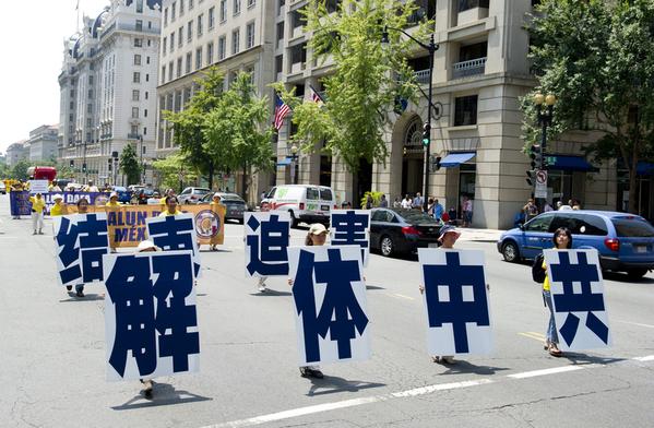 Участники шествия несут иероглифы, означающие «Распад компартии Китая». Фото: The Epoch Times