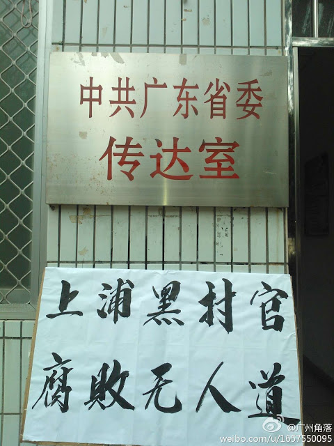 Под табличкой правительственного здания с надписью «Офис обкома партии провинции Гуандун» расположен транспарант с надписью «Чёрные чиновники Шанбу коррумпированы и бесчеловечны». Февраль 2013 года. Фото с molihua.com