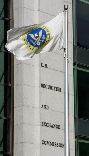 Флаг развевается перед американским зданием Комиссии по ценным бумагам и биржам в Вашингтоне (SEC). В 2011 году SEC приостановила торги некоторых китайских компаний, вышедших на биржу после обратного слияния, так как они искажали предоставляемую информацию. (Chip Somodevilla/Getty Images)