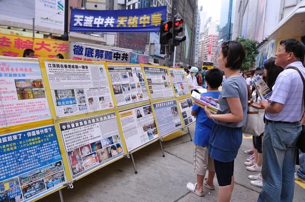 Люди смотрят на стенды с информацией о преследовании последователей Фалуньгун в Китае. Фото: Великая Эпоха (The Epoch Times)