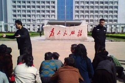 Местные крестьяне на коленях просят чиновников восстановить справедливость  по отношению к ним.  Надпись на камне перед зданием администрации: «Служить народу». Фото с сайта kanzhongguo.com