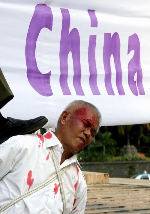 Последователи Фалуньгун из Индонезии демонстрируют сцены жестоких пыток заключённых китайской полицией во время акции протеста в Джакарте 7 октября 2006 года. Фото: Adek Berry/AFP/Getty Images