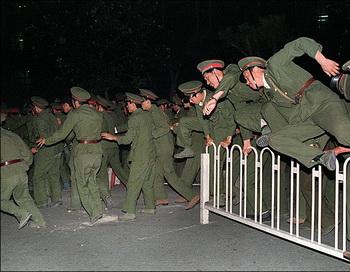 Как китайская коммунистическая партия убедила мир принять её. Солдаты Народно-освободительной армии перепрыгивают через барьер на площади Тянь-Ань-Мэнь в центре Пекина во время кровавого подавления студенческого движения 4 июня 1989 г. Фото: Thomas Cheng/AFP/Getty Images