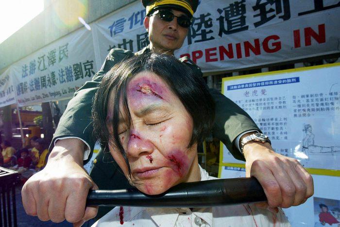 Последователи духовной практики Фалуньгун из Гонконга показывают пытки, применяемые в исправительно-трудовых лагерях и тюрьмах Китая 10 декабря 2004 года. Фото: MIKE CLARKE/AFP/Getty Images