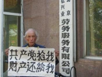 Линь Чженьлянь держит плакат с надписью: «Коммунистическая партия отняла у меня собственность, и она должна вернуть ее обратно». Фото с epochtimes.com