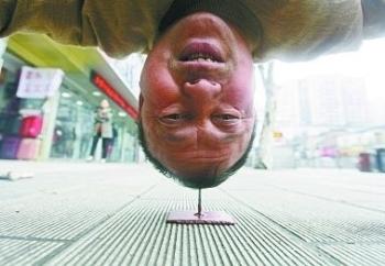 В Китае мужчина стоит вниз головой на острие гвоздя в течение 40 секунд. Фото с epochtimes.com