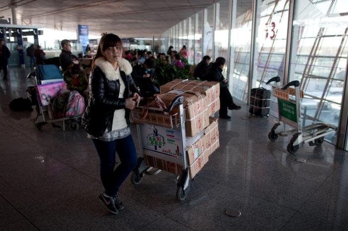 Пассажиры с багажом готовятся к посадке на самолёт. 6 февраля 2013 года, международный аэропорт Пекина. Фото: Ed Jones/AFP/Getty Images